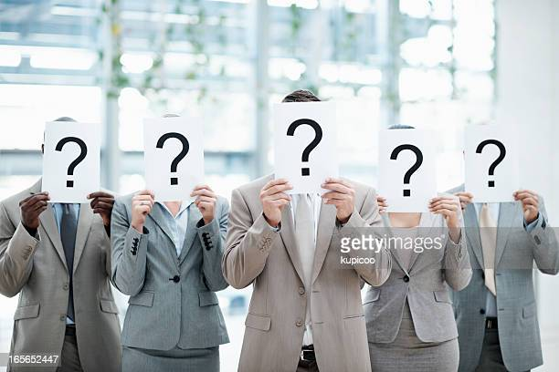 Business people holding sheet with question mark