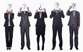 Five business people holding up paper with question mark, obscured face, studio shot