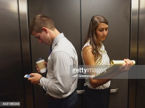 Business people ignoring each other in elevator