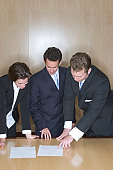 Business People in a board room pointing at a document on the table looking down