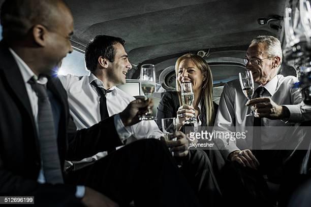 Gens d'affaires de boire du champagne dans une limousine.