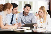 Confident businessmen and businesswomen sitting and working on tablet during a meeting. Business people sitting around the desk in a meeting and watching digital tablet. Portrait of happy colleagues l