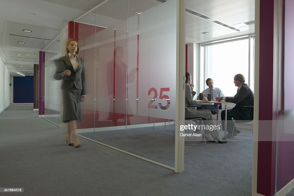 Business People in a Meeting Room and a Businesswoman Walking Past : Stock Photo