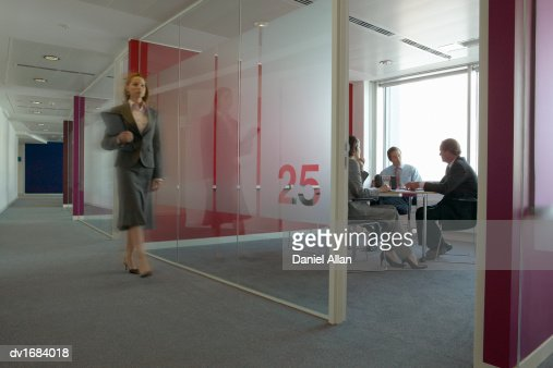 Business People in a Meeting Room and a Businesswoman Walking Past : Bildbanksbilder