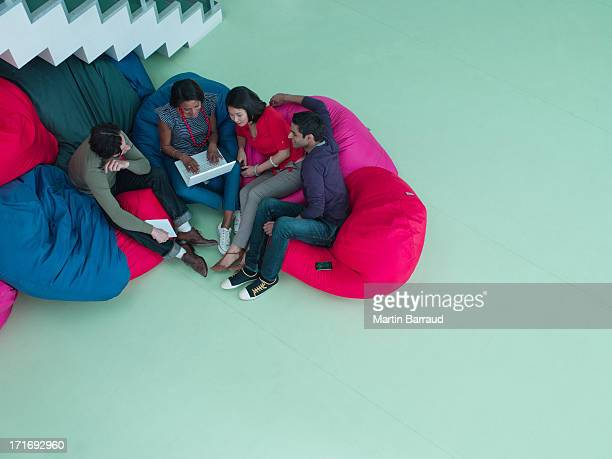 Business people in bean bag chairs looking at laptop