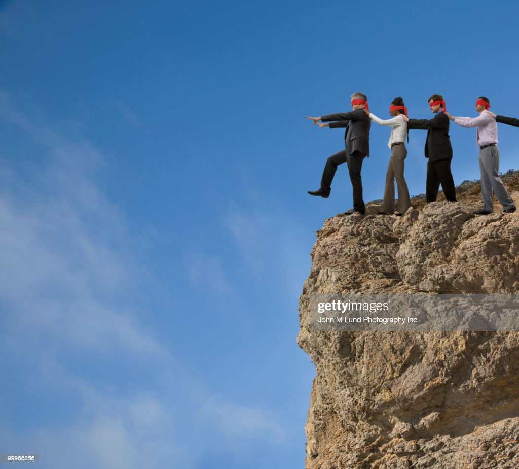 Business people in blindfolds walking off cliff : Stock Photo