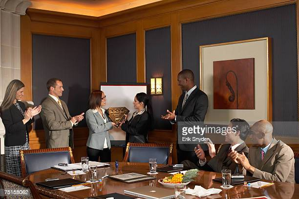 Business people in conference room, business women receiving award while colleagues applaud