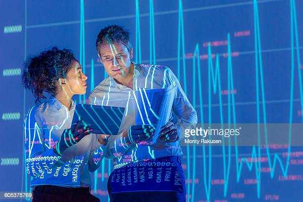 Business people in discussion with graphical data projection