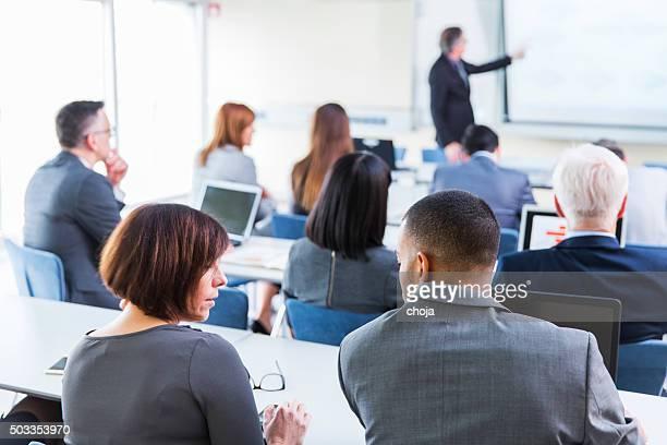 Gens d'affaires l'écoute dans une salle de cours éducation de professeur senior