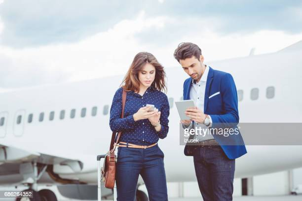 Business people in front of airplane at airport
