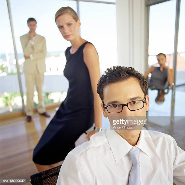 Business people in front of glass wall, portrait, blurred