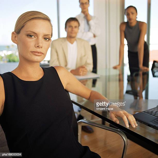 Business people in front of glass wall, portrait