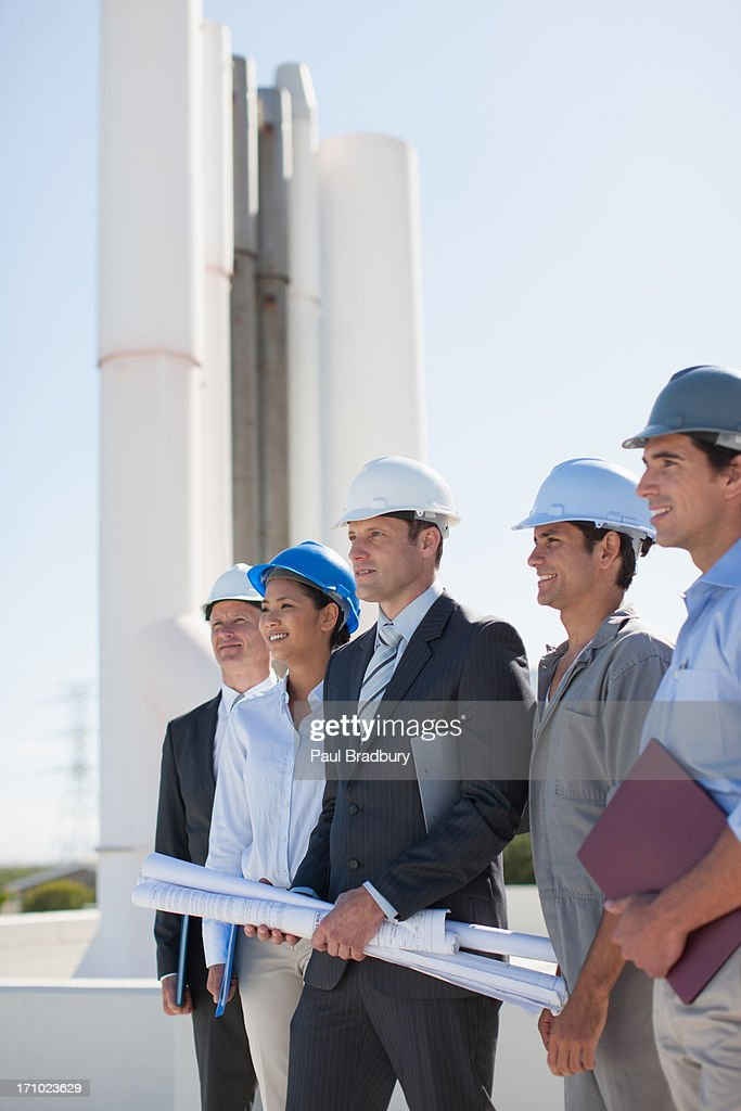 Business people in hard-hats holding blueprints outdoors : Stock Photo