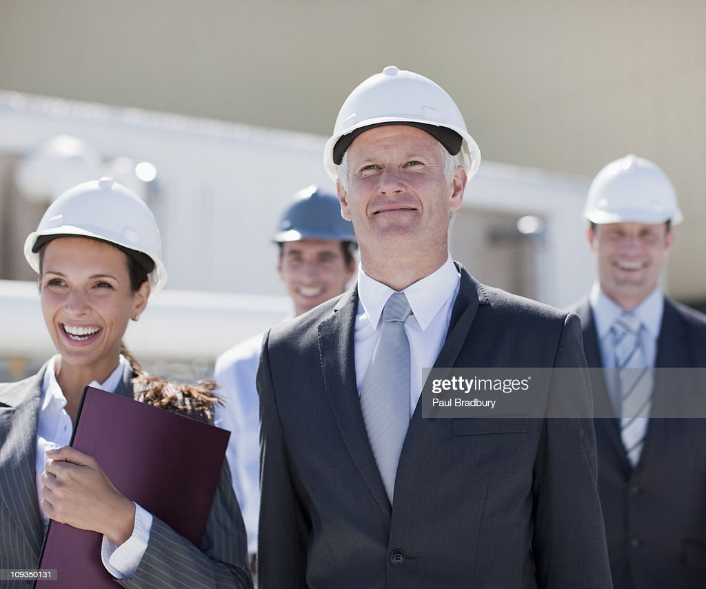 Business people in hard-hats standing together outdoors : Stock Photo