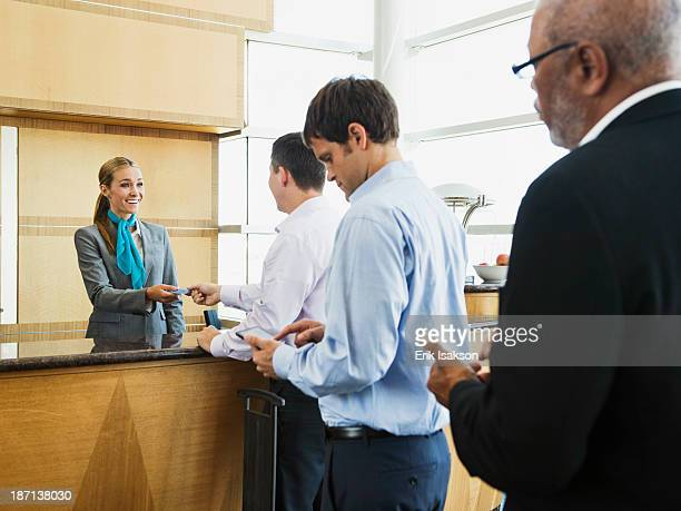 Business people in line at airport front desk