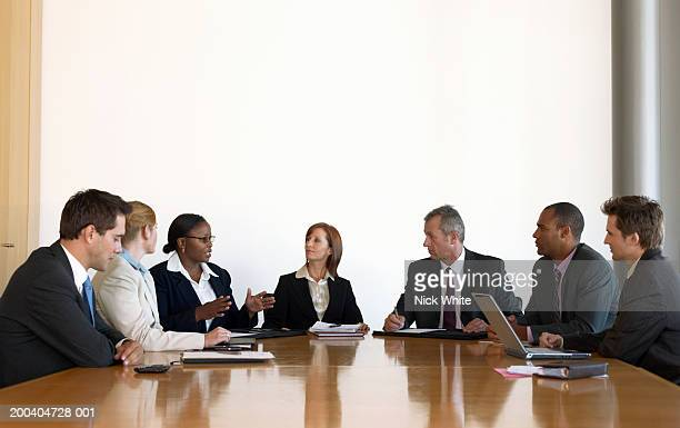 Business people in meeting looking at woman making hand gestures