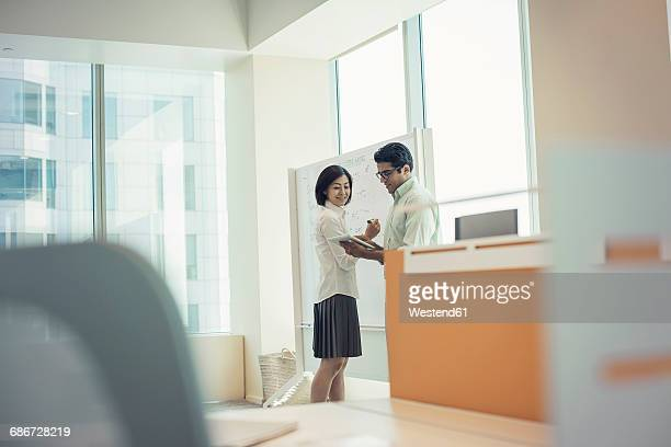 Business people in office working at whiteboard