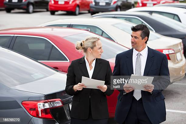 Business people in parking lot.