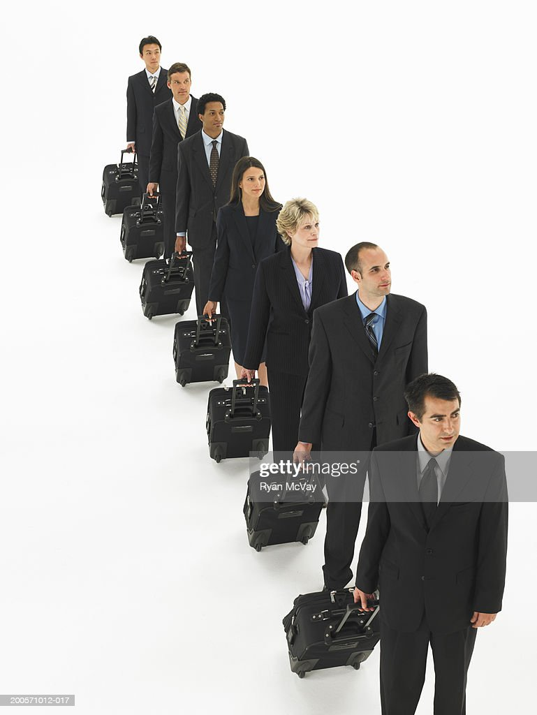 Business people in row, pulling suitcases, elevated view : Stock Photo