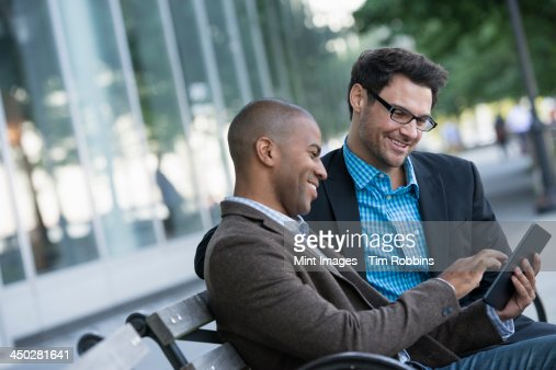 Business people in the city. Keeping in touch on the move. Two men seated on a park bench outdoors, looking at a digital tablet.