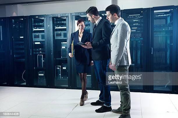 Business people in the server room checking systems