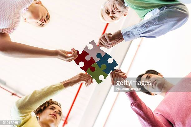Business People Joining Jigsaw Pieces In Office