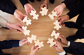 Directly above shot of business people joining jigsaw puzzle pieces in office