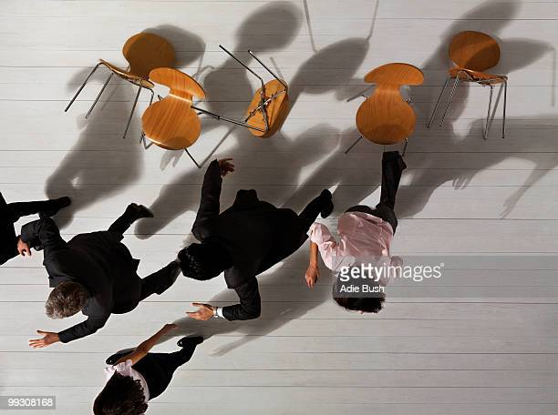Business people knocking over chairs