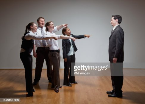 Business people laughing at man : Stock Photo