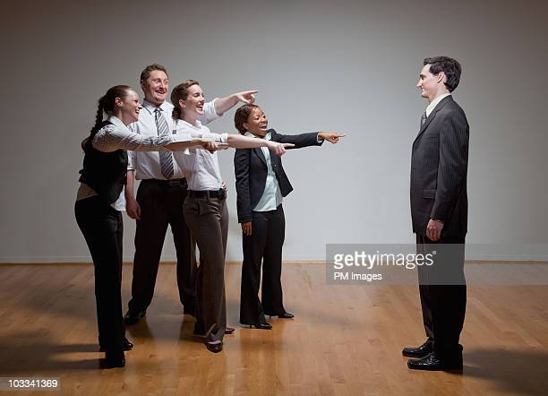 Business people laughing at man