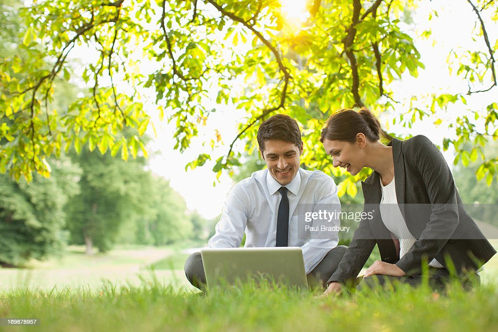 Business people laying in grass using laptop : Stock Photo