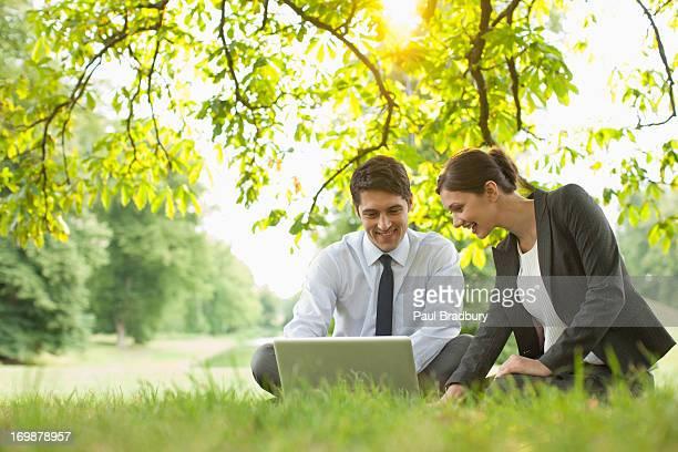 Las personas de negocios que descansan en hierba usando computadora portátil