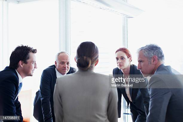 Business people leaning in circle and talking