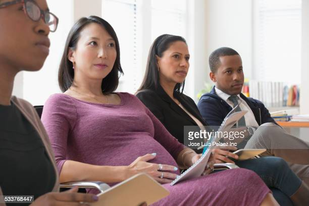 Business people listening in presentation in office