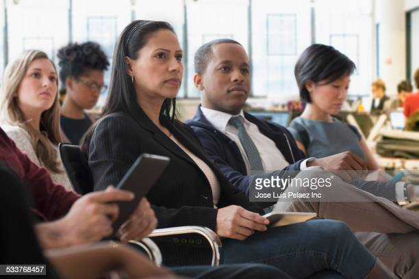 Business people listening to presentation in office