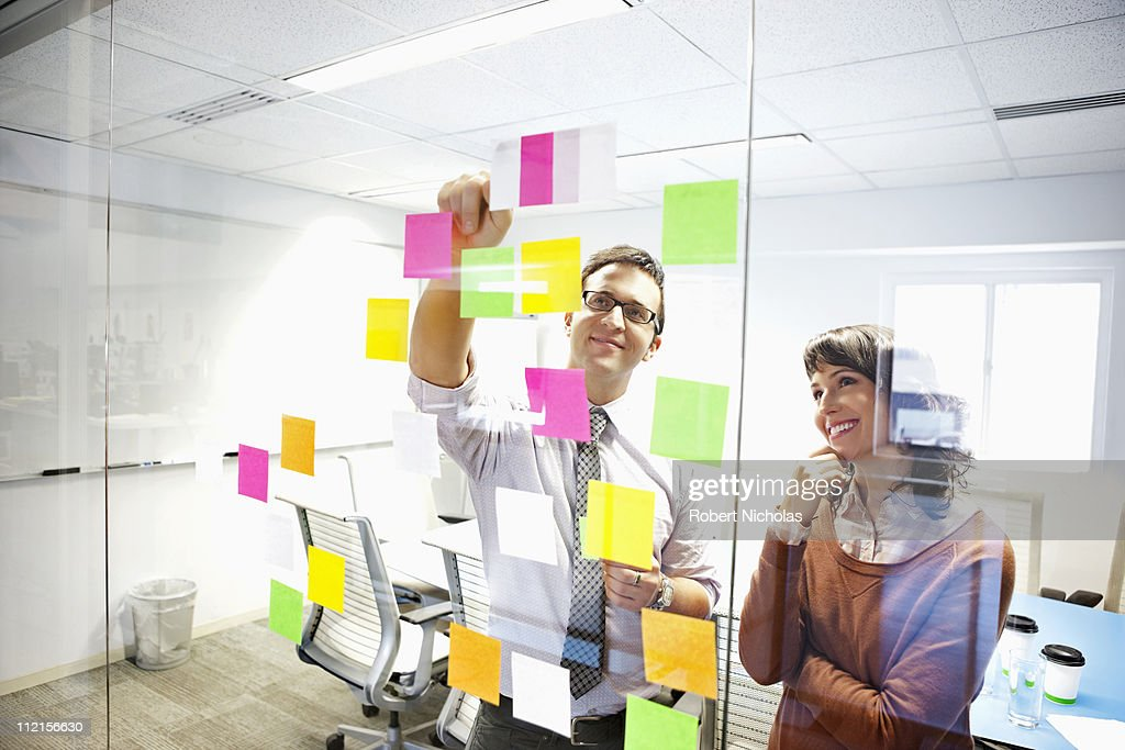 Business people looking at adhesive notes in conference room : Stock Photo