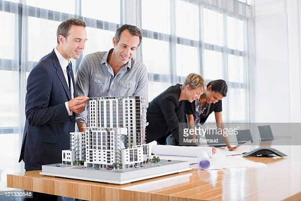 Business people looking at blueprints and model building
