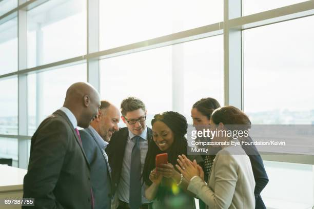 Business people looking at cell phone in office