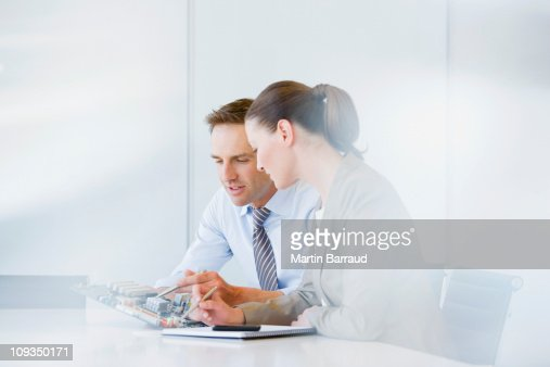 Business people looking at circuit board in office : Stock Photo