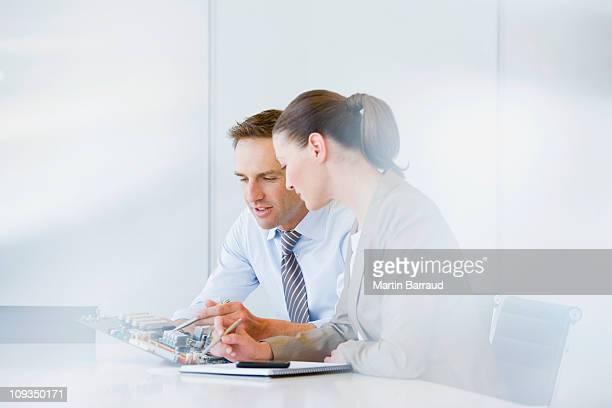 Negócios pessoas Olhando para a placa de circuito no escritório