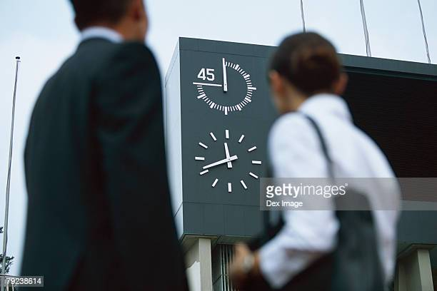 Business people looking at clock on stadium sign display