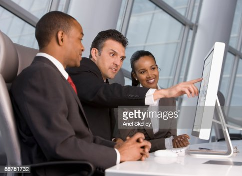 Business people looking at computer monitor : Stock Photo