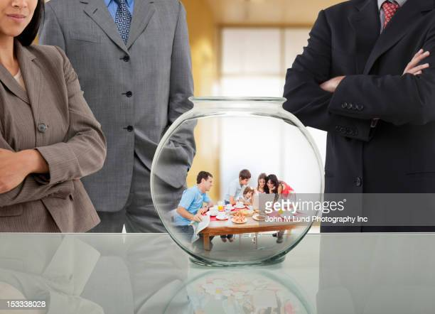 Business people looking at family in fishbowl