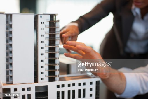 Business people looking at model building : Stock Photo