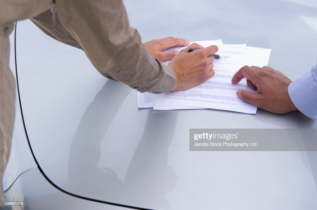 Business people looking at paperwork in parking lot : Stock Photo