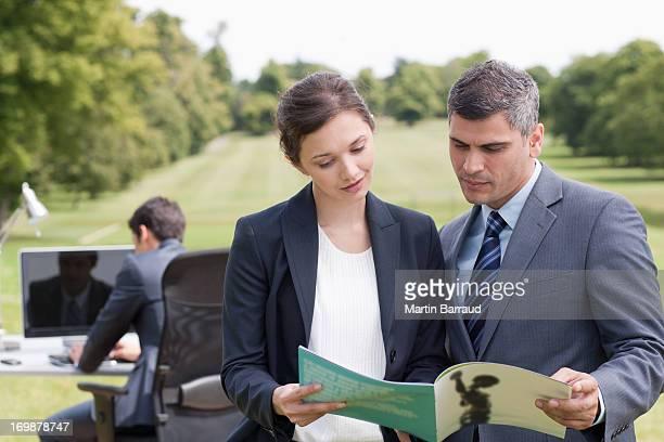 Business persone guardare report insieme all'aperto