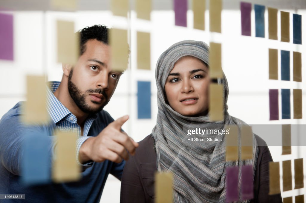 Business people looking at sticky notes in office
