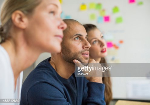 Business people looking away in creative office
