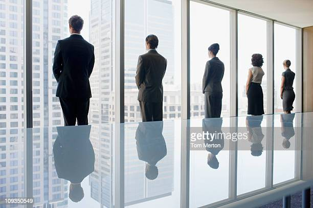 Business people looking out conference room window together
