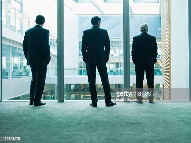 Business people looking out glass wall together